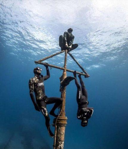 trois apneistes pendus au mat d'une épave sous marine, photo sous marine, chasseur sous marin