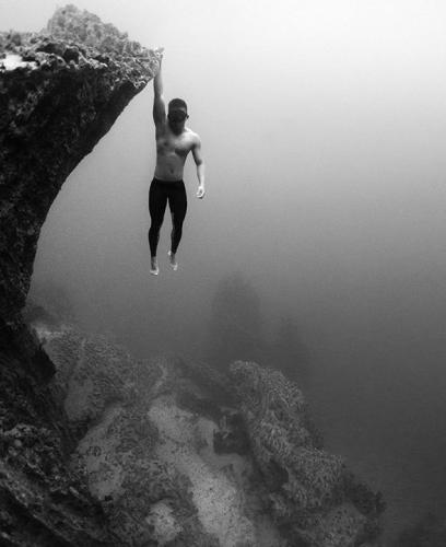 apneiste martin zapanta, photo sousmarine d'un apneiste accroché à une colline sous marine
